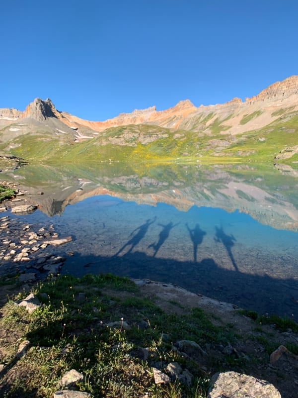 silhouettes at ice lake and mountain lake reflection
