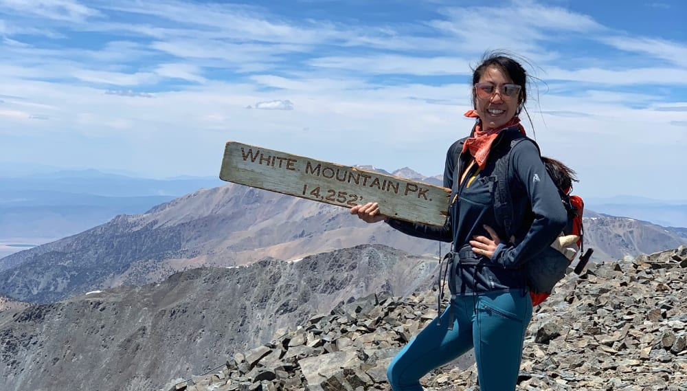 girl and white mountain summit sign 14252